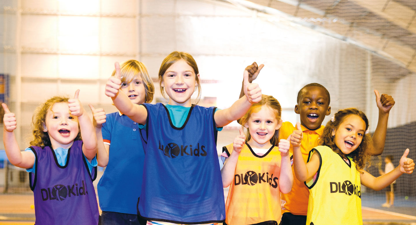 Group of children wearing DL Kids vests, giving a thumbs up. Part of the DL Kids Summer Holiday Camp.