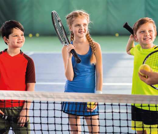 3 children playing tennis as part of DL Kids Summer Holiday Clubs.