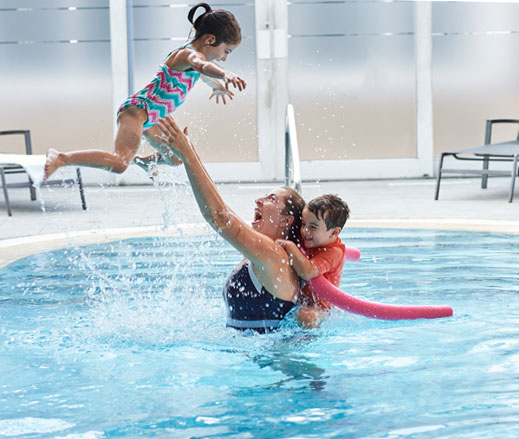 Image of a woman with two young children in a David Lloyd swimming pool