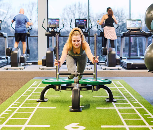 Image of woman pushing a sled in the gym at David Lloyd