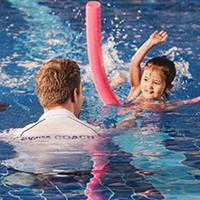 A young girl being coached how to swim by an instructor.